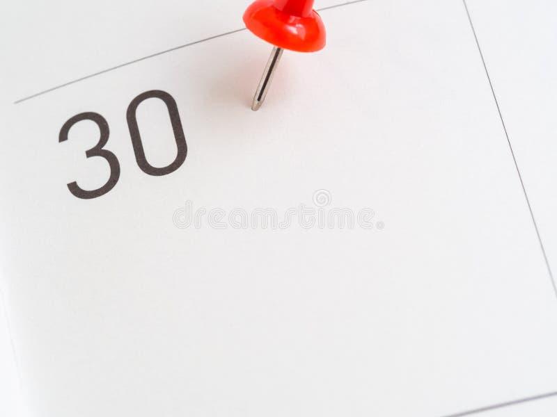Perno rosso su una carta di 30 calendari fotografia stock libera da diritti