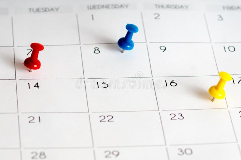 Pernos amarillos azules rojos en calendario imagen de archivo libre de regalías