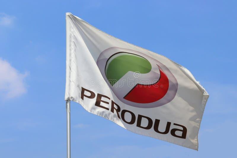 Perodua Flag Flying Under A Blue Sky. The logo and emblem on the flag of the Malaysian car manufacturer Perodua flying under a blue sky stock photos
