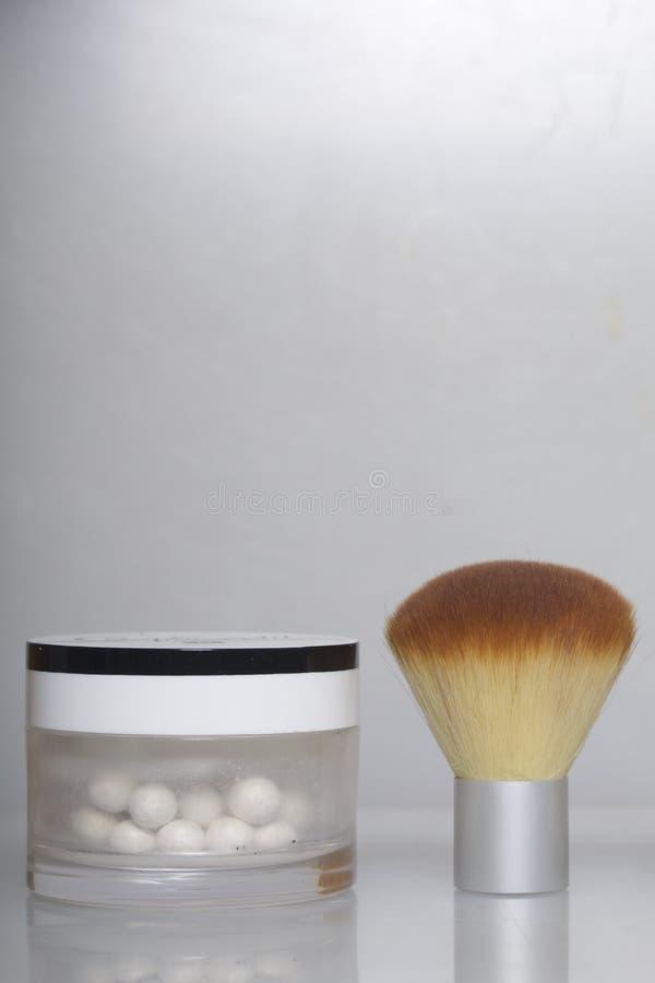 Perolize o highlighter sob a forma das bolas em um frasco aberto Ao lado dela é uma escova cosmética para aplicá-la Em um fundo b imagens de stock royalty free