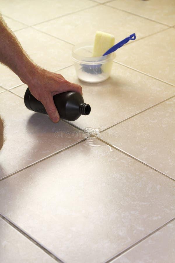 Perossido di idrogeno di versamento sulla malta liquida del pavimento fotografia stock