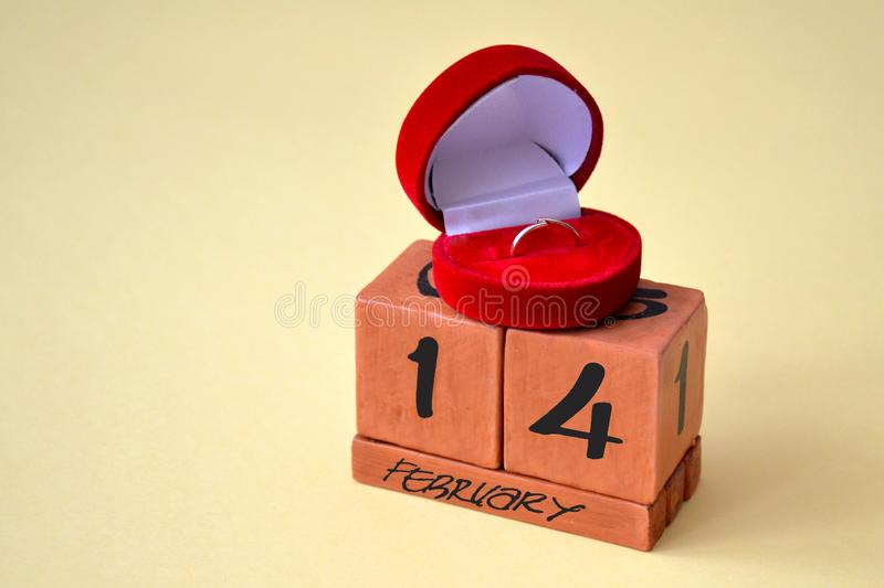 A perpetual calendar with February 14 and a red velvet gift box with a gold diamond ring. Concept of love and Valentines Day stock image