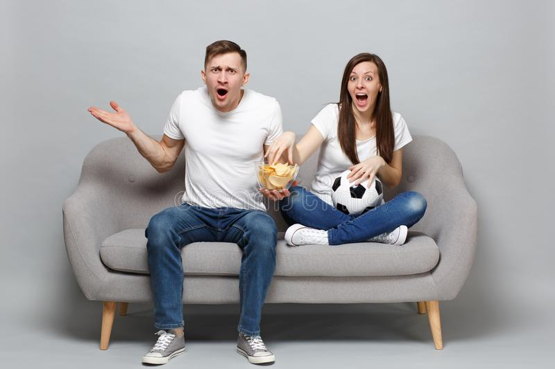 Perplexed couple woman man football fans cheer up support favorite team with soccer ball, hold glass bowl of chips. Perplexed couple women men football fans royalty free stock image