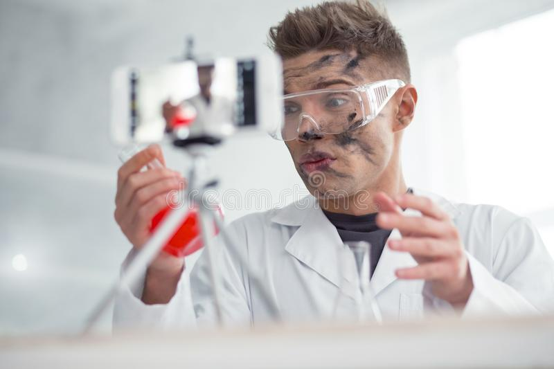 Perplexed dirty blogger after the experiment. I am angry. Good-looking baffled fair-haired young blogger wearing uniform and holding a test tube while making new stock image