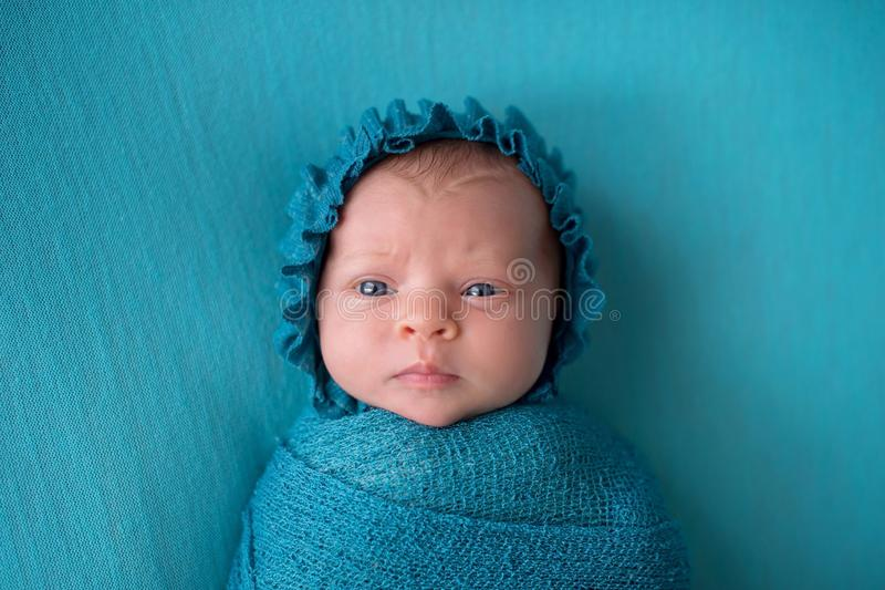 Perplexed Newborn Baby Girl Wearing a Turquoise Blue Bonnet. An alert, three week old, newborn baby girl wearing a turquoise blue bonnet with a perplexed royalty free stock photography