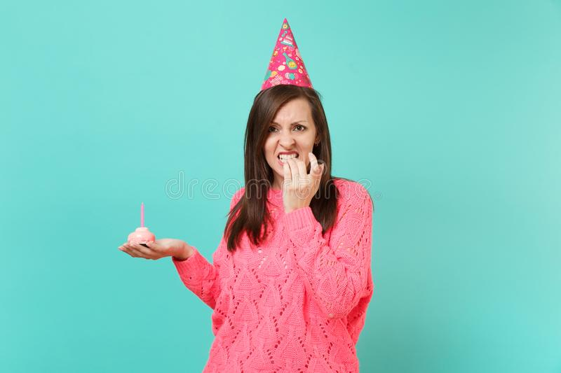 Perplexed young woman in knitted pink sweater, birthday hat gnawing nails, hold in hand cake with candle isolated on. Blue wall background studio portrait stock image