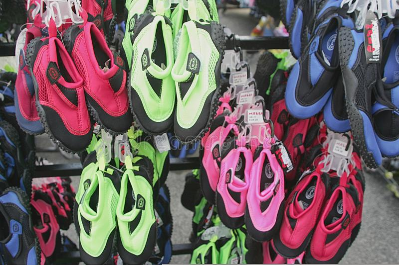 Perranporth, Cornwall, UK - April 9 2018: Reef shoes or aqua shoes hanging up for sale outside a surf shop, in red, blue, green p stock photos