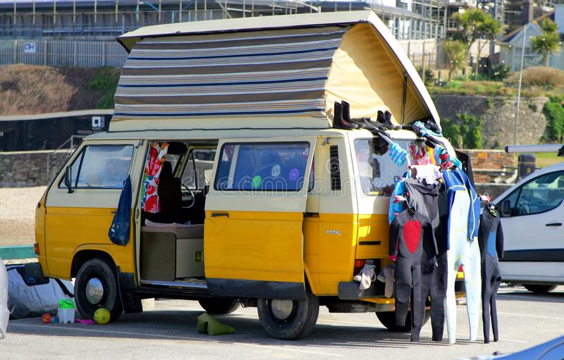 Perranporth, Cornwall, UK - April 9 2018: Yellow VW or VolksWagen camper van with roof extended, with wetsuits and surf gear outs royalty free stock image
