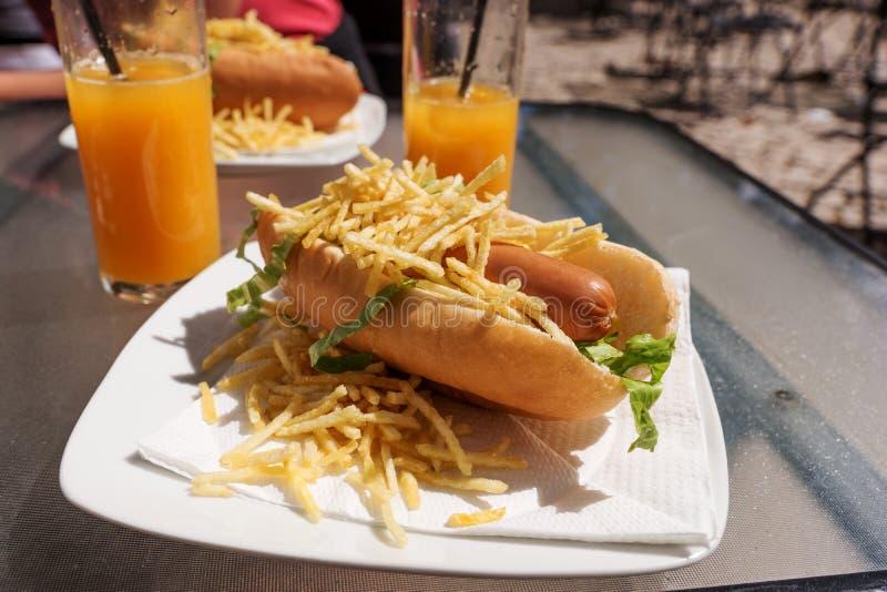 Perrito caliente con las patatas fritas y el zumo de naranja imagen de archivo libre de regalías