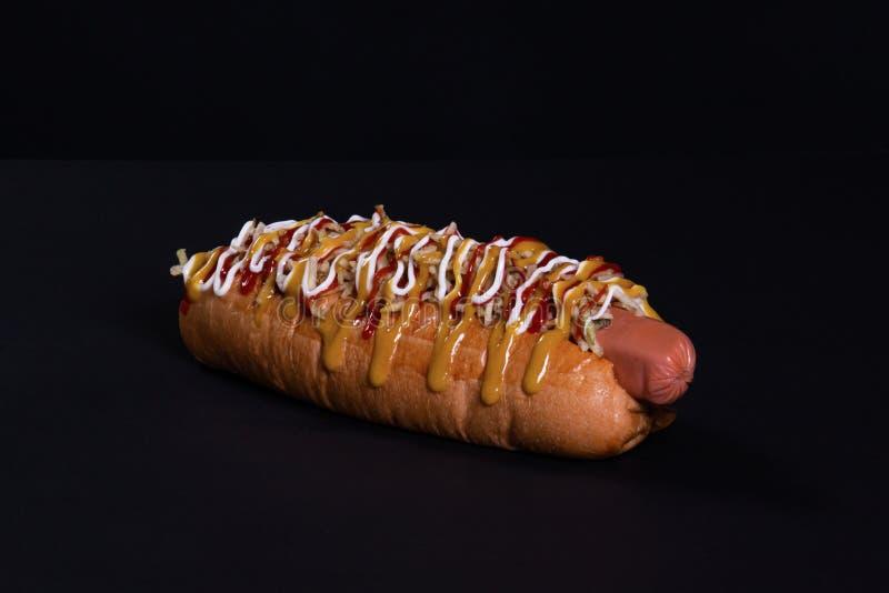 Perrito caliente delicioso con las salsas y las naves fritas de la patata fotos de archivo