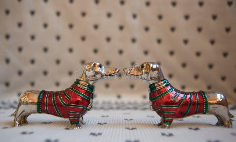 Perro basset dos en suéter rojo-verde de la Navidad en fondo manchado foto de archivo