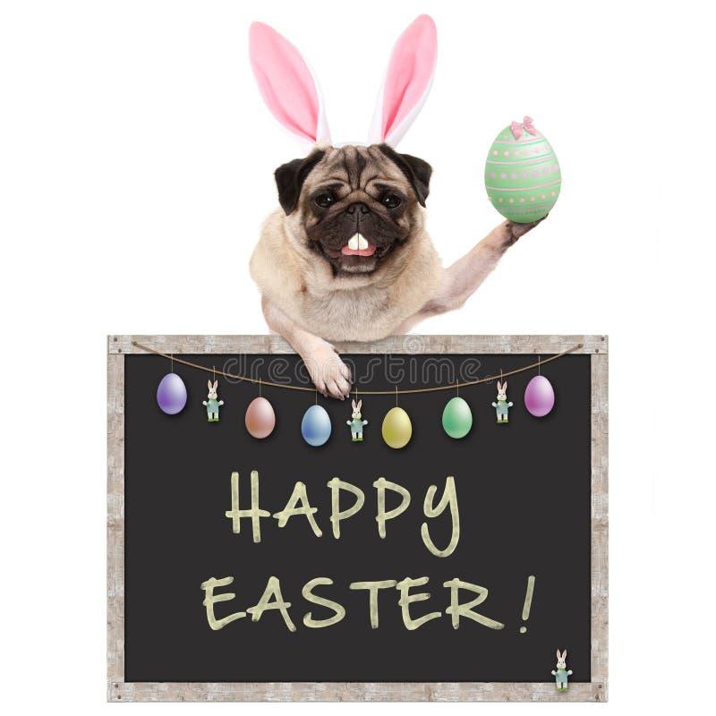 Perro de perrito lindo del barro amasado con la diadema de los oídos del conejito, soportando la ejecución del huevo de Pascua co fotos de archivo libres de regalías