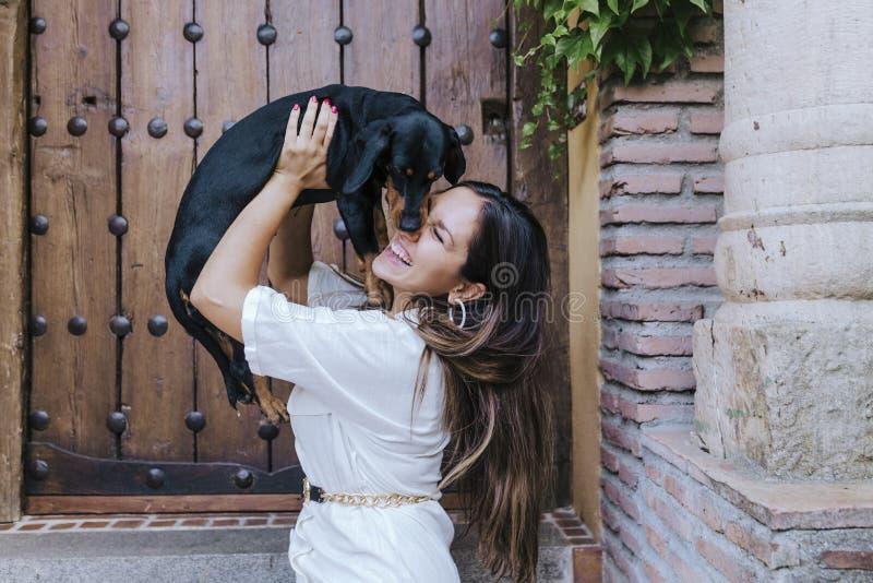 Perro de salchicha cortado sentado afuera con su dueño en casa. adorable dueño del beso de perro. Amor para el concepto de los a imagen de archivo