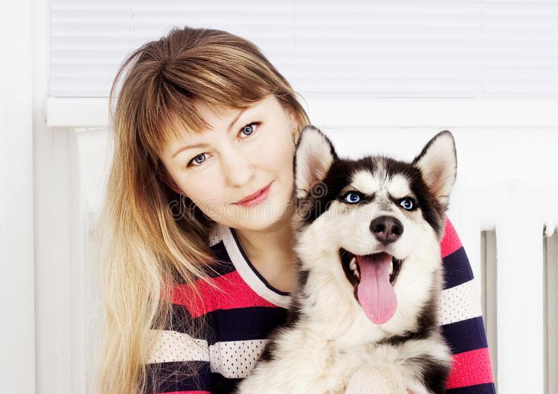 Perro esquimal de la mujer y del perro, abrazando foto de archivo