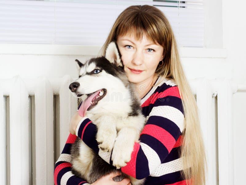 Perro esquimal de la mujer y del perro, abrazando imágenes de archivo libres de regalías
