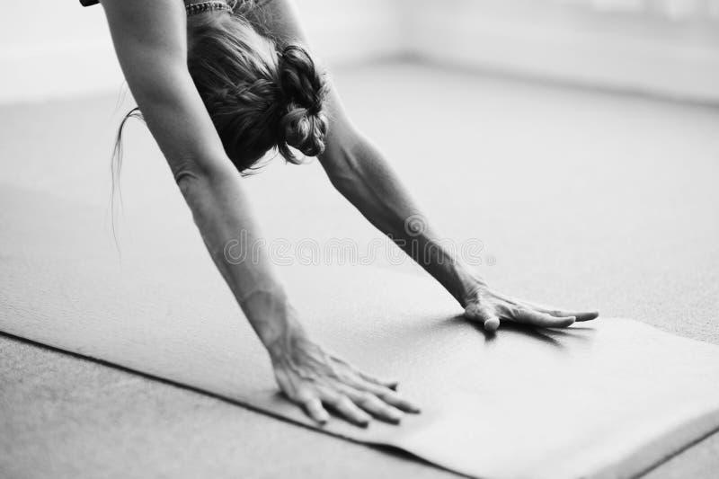 Perro hacia abajo de la fotografía de la mujer blanco y negro de la yoga fotos de archivo