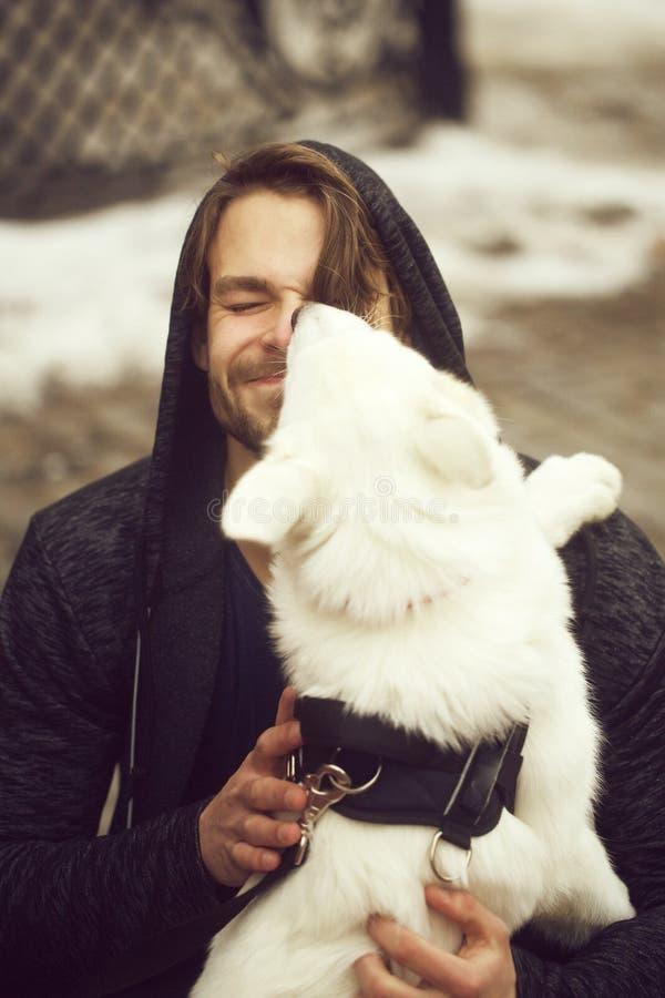 Perro lindo que lame la cara del hombre feliz del perrito imagen de archivo