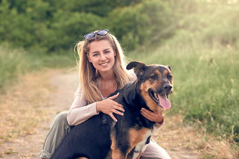 Perro negro sonriente feliz que lleva un arnés que camina que se sienta haciendo frente a su dueño de la mujer bastante joven imágenes de archivo libres de regalías