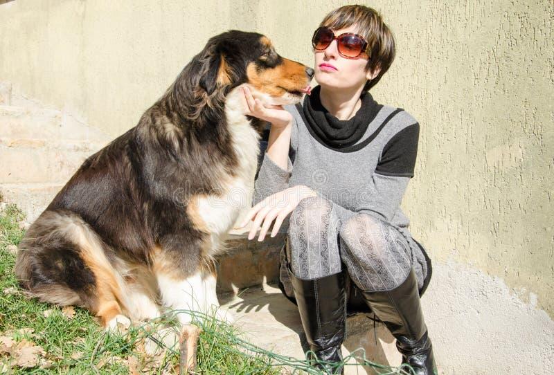 Perro de pastor australiano que besa a la señora de la moda fotografía de archivo