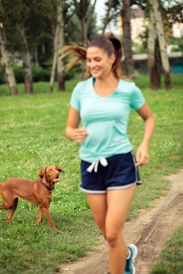 Perro que sigue a la mujer joven mientras que ella está corriendo en un parque imagen de archivo libre de regalías