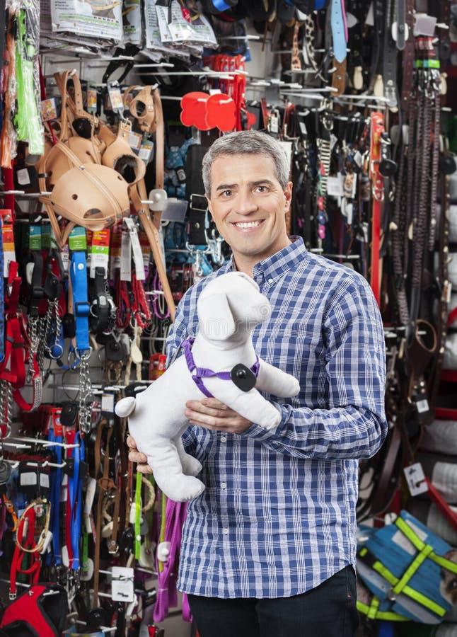 Perro relleno tenencia del cliente en la tienda del animal doméstico imagen de archivo libre de regalías