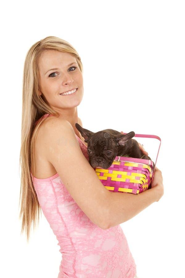 Perro rosado de la cesta de Pascua del top sin mangas de la mujer en brazos fotos de archivo
