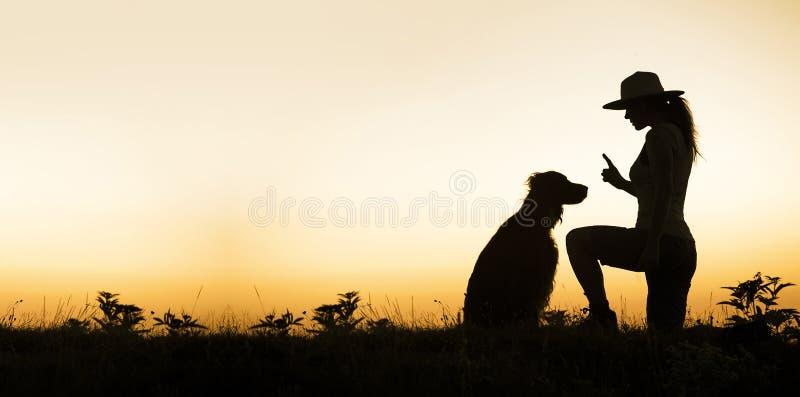 Perro y su instructor - siluetee la imagen con el espacio en blanco, copian el espacio fotos de archivo