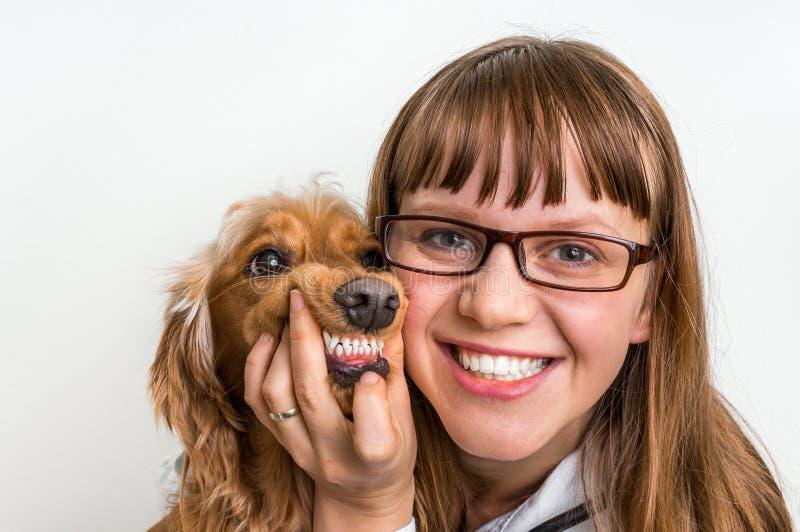 Perro y veterinario sonrientes divertidos en clínica veterinaria imagenes de archivo