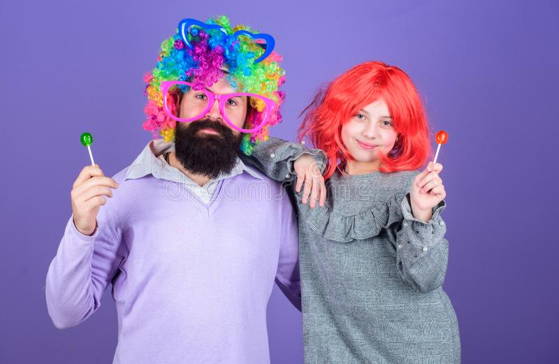 Perruque colorée barbue d'usage de père et de fille d'homme tandis que mangez la sucrerie de lucette Père aimant de chose faire p photos stock