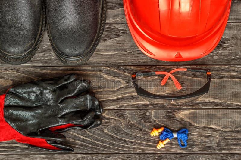 Persönliche Schutzausrüstung: schwarze Handschuhe schützen die Gläser des Sturzhelms auf einem hölzernen Hintergrund stockbilder