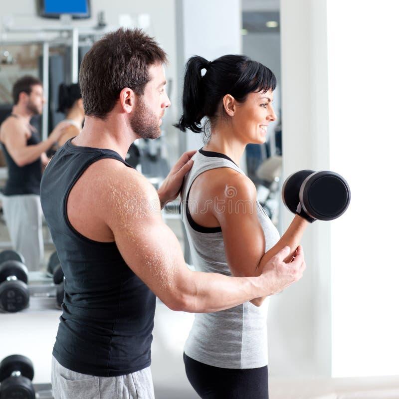 Persönlicher Kursleiter der Gymnastikfrau mit Gewichttraining lizenzfreie stockfotografie