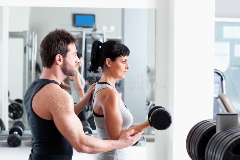 Persönlicher Kursleiter der Gymnastikfrau mit Gewichttraining lizenzfreies stockfoto