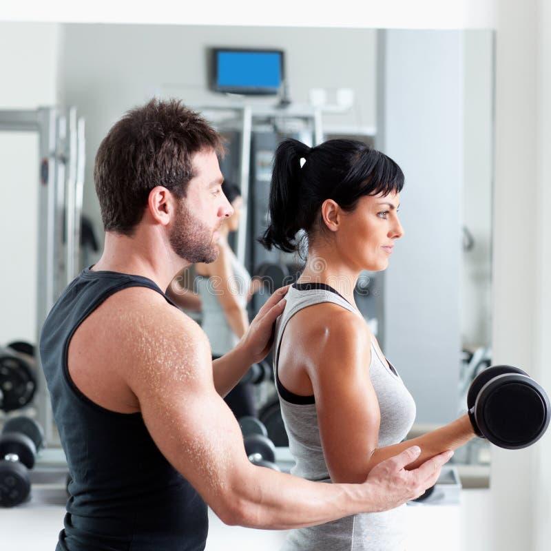 Persönlicher Kursleiter der Gymnastikfrau mit Gewichttraining lizenzfreie stockfotos