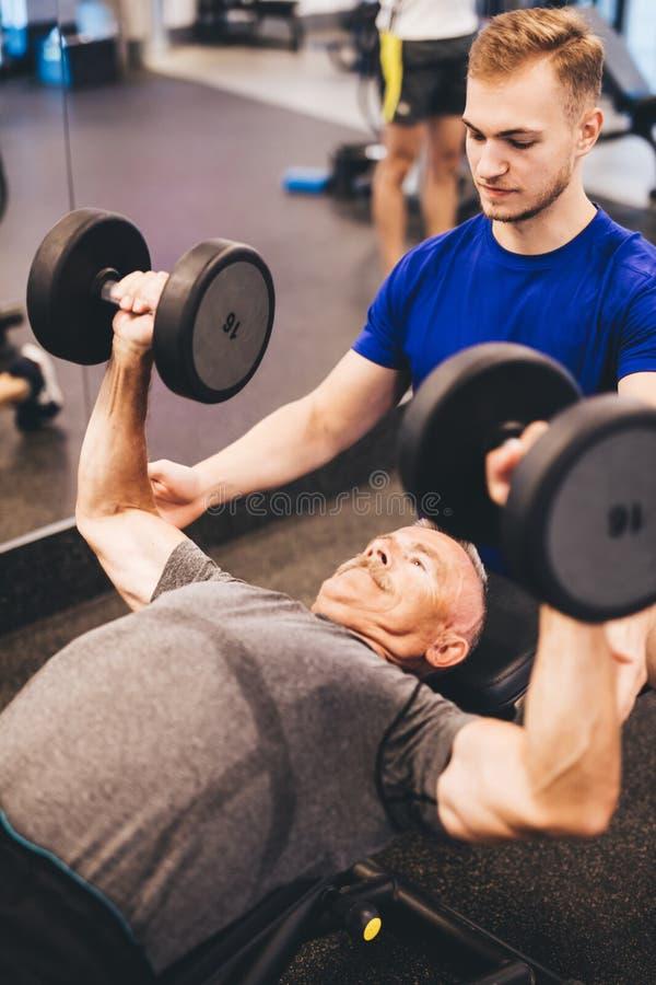 Persönlicher Trainer, der älteren Mann in einer Übung unterstützt lizenzfreie stockfotos