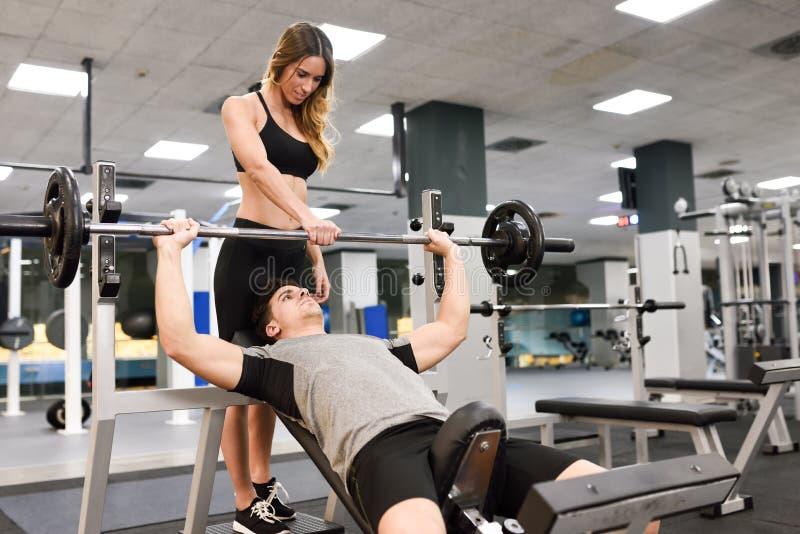 Persönlicher Trainer, der einem jungen Mann hilft, Gewichte anzuheben stockbilder