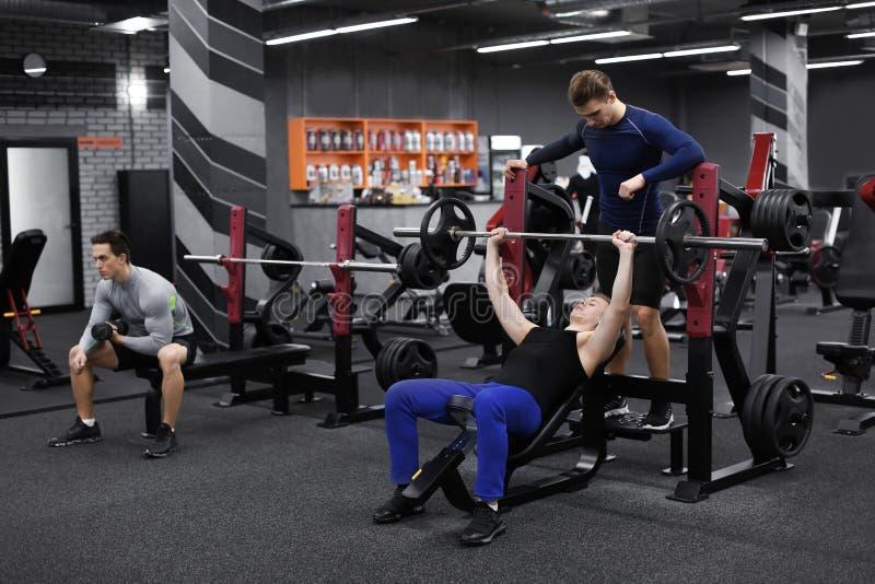 Persönlicher Trainer, der jungem Mann hilft, der in der Turnhalle ausarbeitet lizenzfreies stockfoto