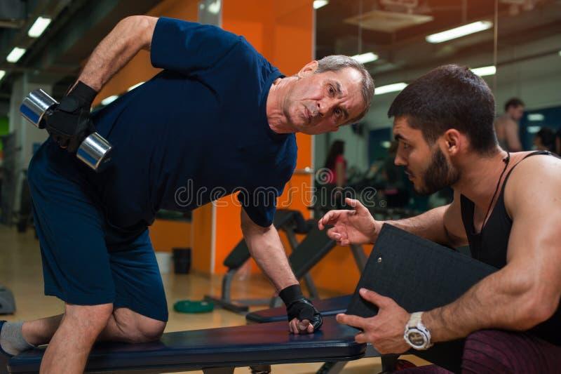 Persönlicher Trainer, der mit älterem Mann in der Turnhalle arbeitet lizenzfreies stockfoto