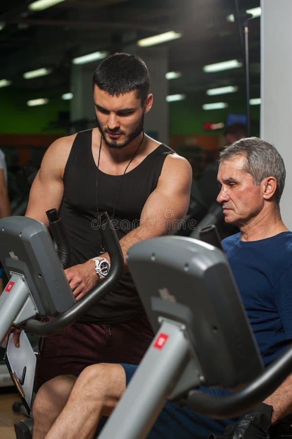 Persönlicher Trainer, der mit älterem Mann in der Turnhalle arbeitet stockbild