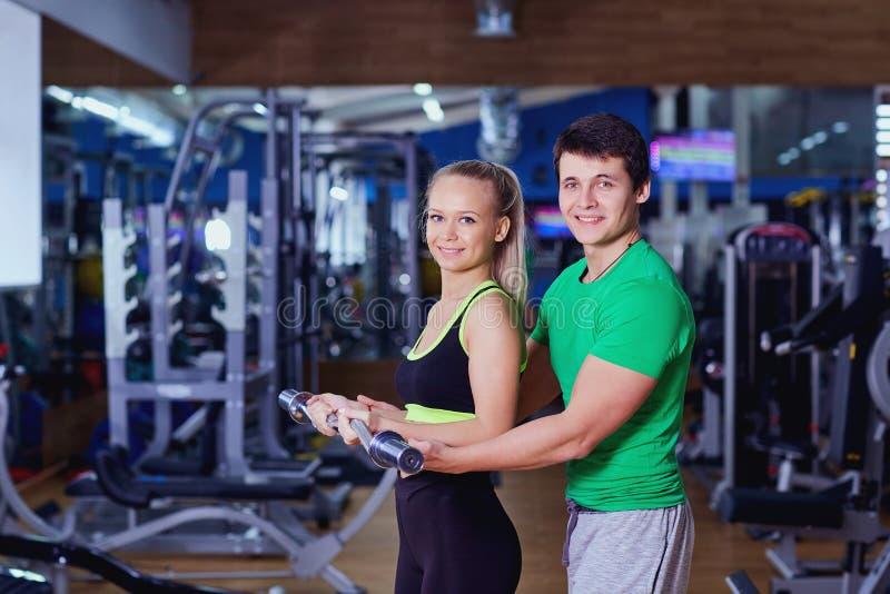 Persönlicher Trainer hilft anhebenden Gewichten eines Mädchens in der Turnhalle stockbild