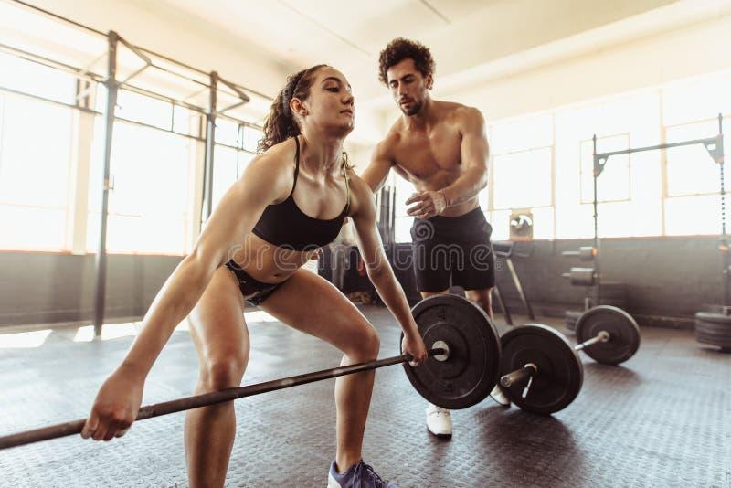 Persönlicher Trainer mit Frau anhebendem Barbell lizenzfreie stockbilder