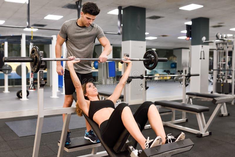 Persönlicher Trainer, welche einer jungen Frau hilft, Gewichte anzuheben lizenzfreie stockfotografie