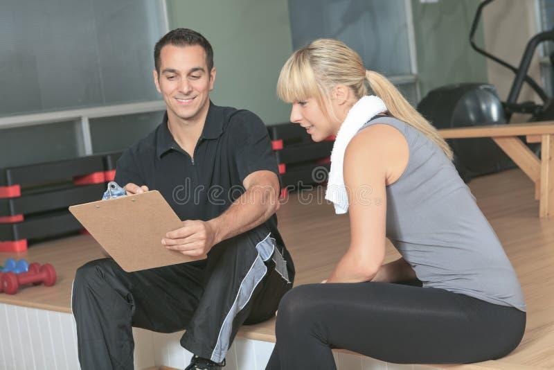 Persönlicher Trainermann der Turnhallenfrau mit Gewicht stockfoto