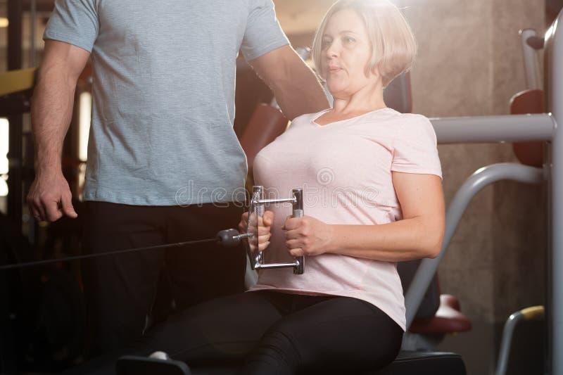 Persönlicher Trainermann hilft einer älteren Frau stockbild