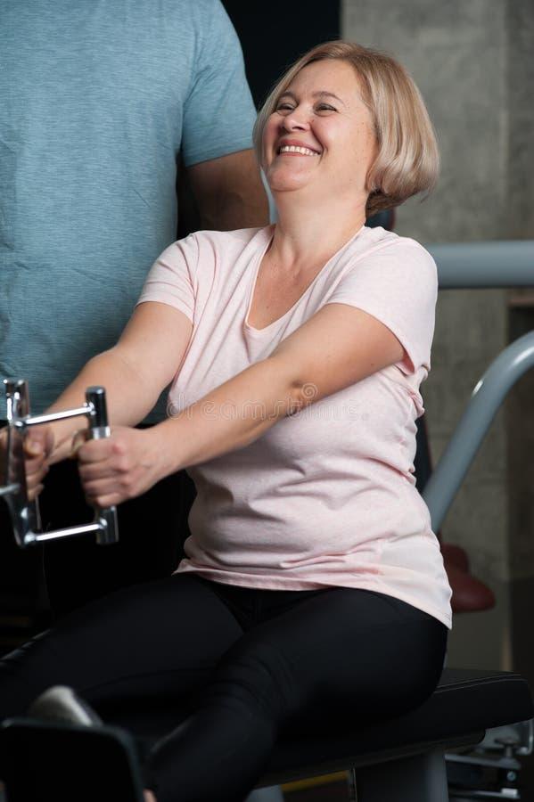 Persönlicher Trainermann hilft einer älteren Frau lizenzfreie stockbilder