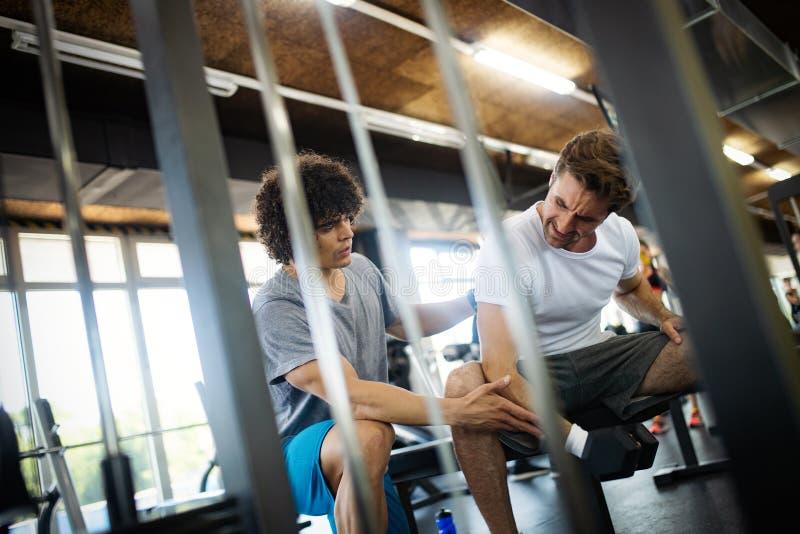 Pers?nlicher Trainermann der Turnhalle mit GewichtsAusbildungsanlageen stockbild