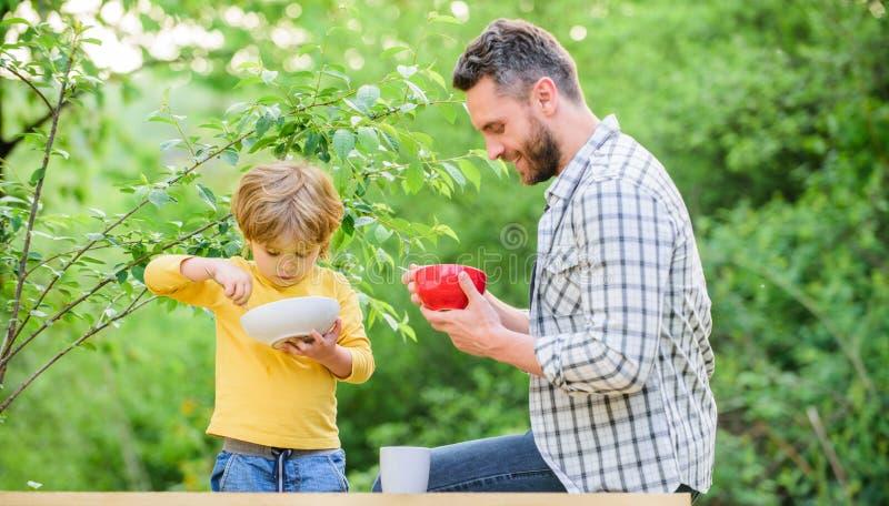 Pers?nliches Beispiel Vater unterrichten Sohn, Naturkost zu essen Wenig Junge und Vati essen Nahrungskinder und -erwachsene organ lizenzfreie stockfotografie