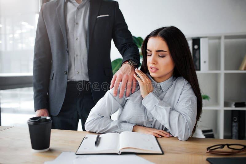 Perseguição do conceito A jovem mulher receosa senta-se na tabela A perseguição sai de seu chefe Mantém a mão em seu ombro guy imagens de stock royalty free