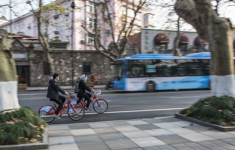 Perseguindo homens novos e mulheres que montam bicicletas públicas, o homem claro e assuntos fêmeas, fundo borrado da rua imagens de stock royalty free