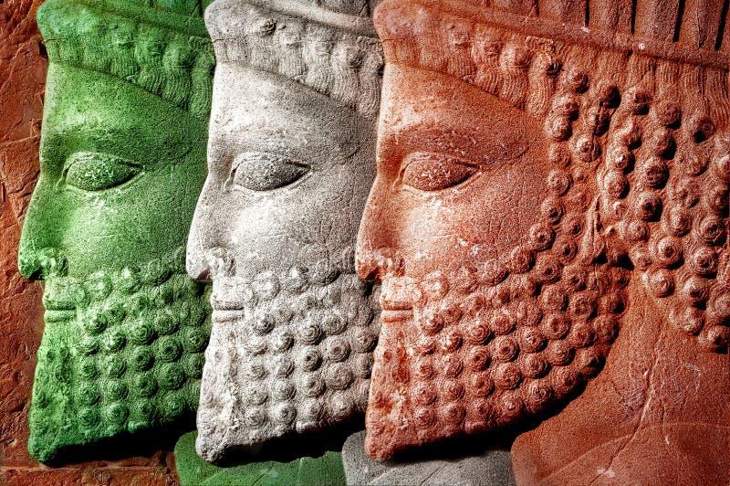 persepolis irã Pérsia antiga o Bas-relevo cinzelou nas paredes de construções velhas Cores da bandeira nacional de Irã imagens de stock