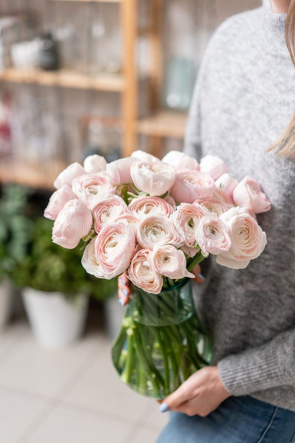 Persian buttercup in glass vases in womens hands. Bunch pale pink. the concept of a florist in a flower shop. Wallpaper. Many layered petals. Persian buttercup stock photo